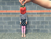 Child with large strawberry in front of face