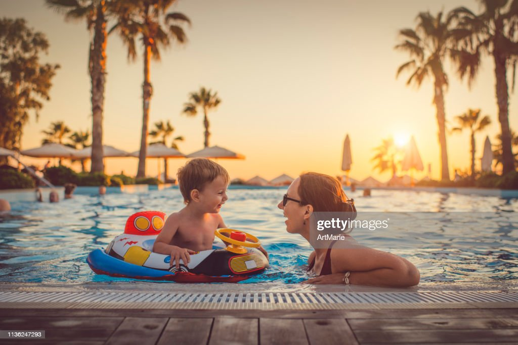 Child with mother in swimming pool, holiday resort : Stock Photo