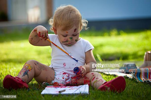 Child with paint brush and paints