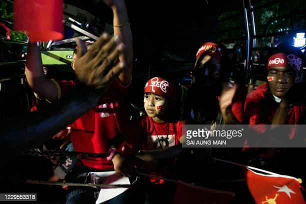 Child with paint on his face looks on as supporters of the National League for Democracy party celebrate in front of the party's headquarters in...