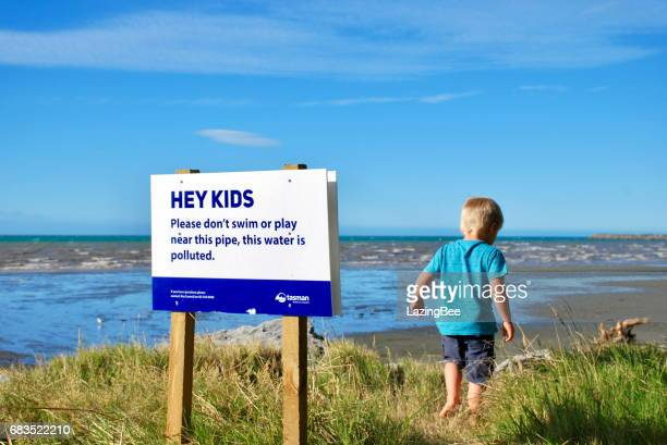 Child with Polluted Water Warning Signpost, Pohara Beach, Takaka, Taman District, New Zealand