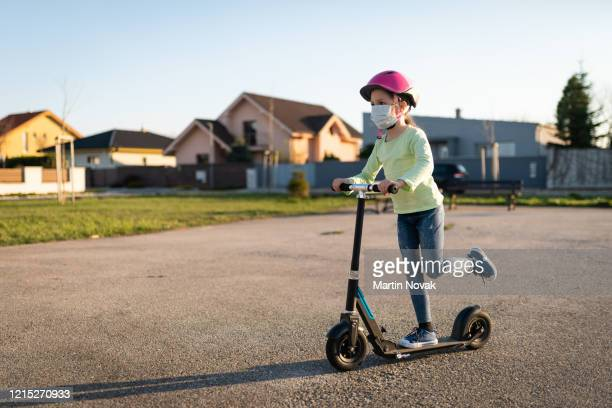 child with protective face mask riding on scooter - pandemic illness stock pictures, royalty-free photos & images