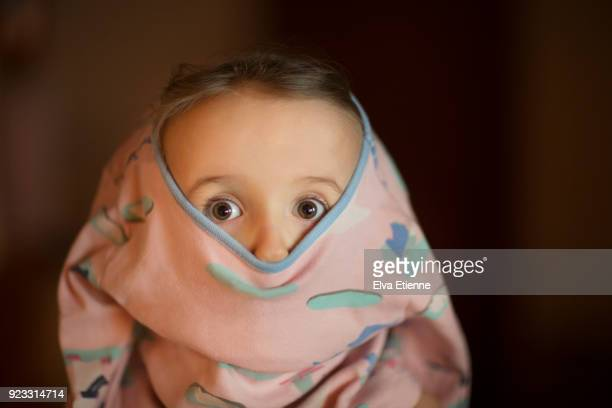Child with raised eyebrows and head stuck partially in pyjamas
