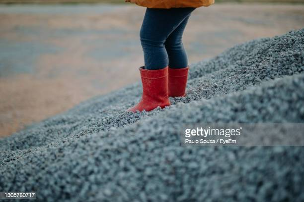 child with red rubber boots - boot stock pictures, royalty-free photos & images