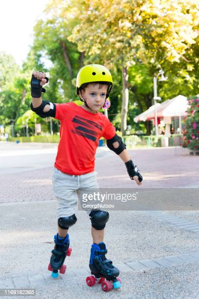 child with roller skates in a sunny summer park. - guardsman stock pictures, royalty-free photos & images