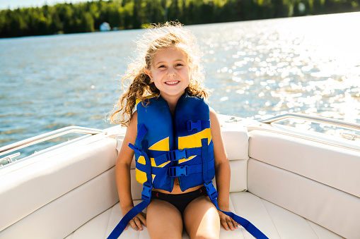 child with safety vest on the lake boat 1070509738