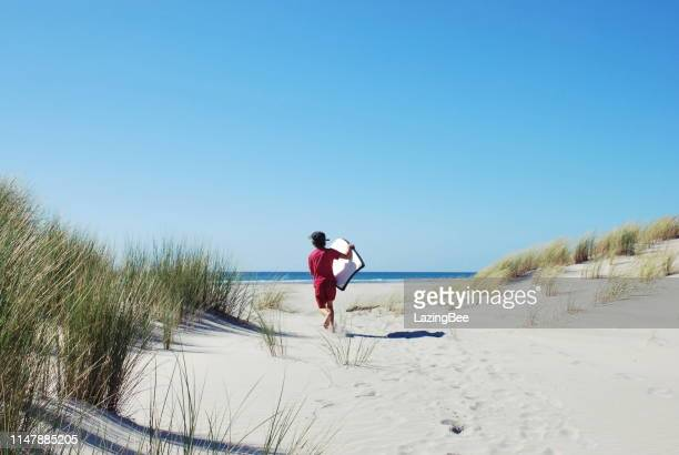 child with sand board in dunes - new zealand stock pictures, royalty-free photos & images