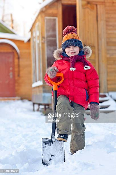 Child with shovel in winter