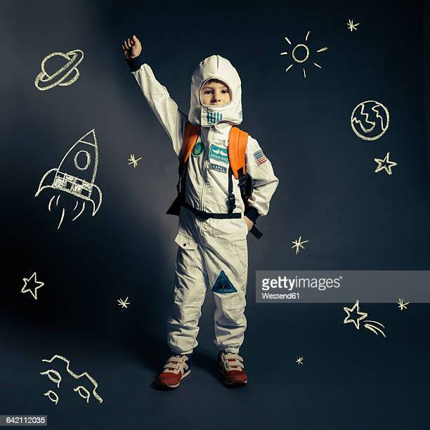 child with spacesuit orbited by celestial bodies and luminaries - children only stock pictures, royalty-free photos & images