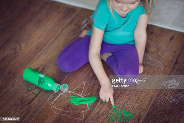 child with spilled green paint on wooden floor - 4 girls finger painting stock pictures, royalty-free photos & images