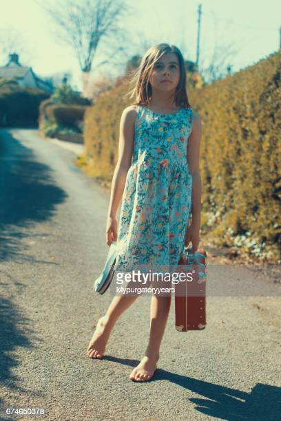 child with suitcase - barefoot girl stock photos and pictures