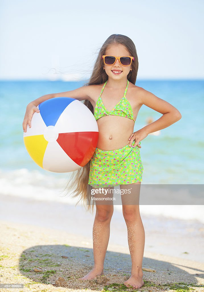 child with sunglasses and ball at the beach : Stock Photo