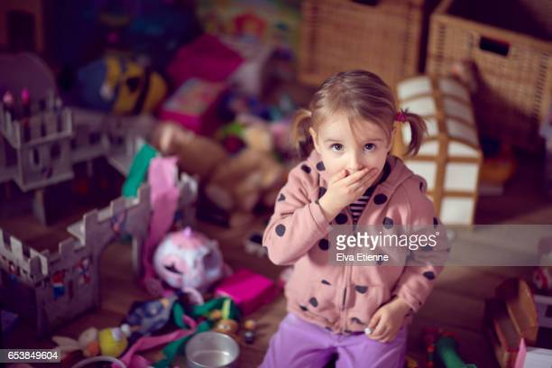 Child with surprised expression, in a messy bedroom