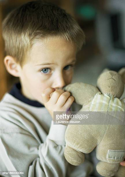 Child with thumb in mouth holding stuffed animal, portrait