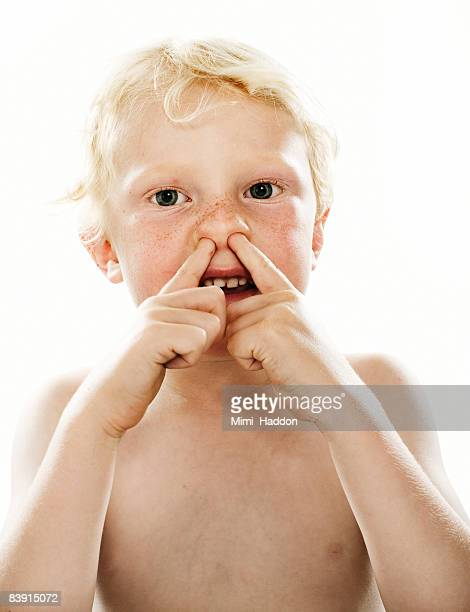 child with two fingers up his nose