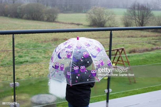 Child with umbrella outdoors in the rain