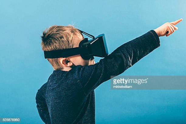 Child with VR glasses points hand out in the air