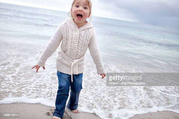 Child with wet feet at the beach, Australia