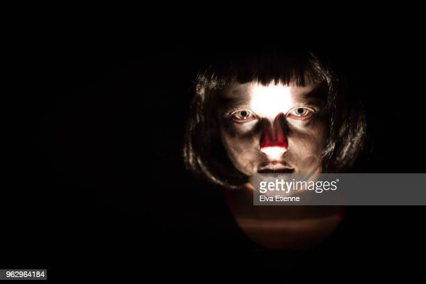 child with zombie face paints, in the dark, staring ominously and intensely - halloween zombie makeup stock photos and pictures