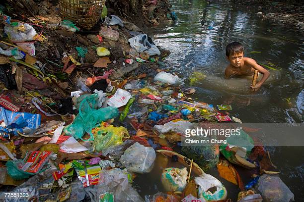 A child worker scavenges garbage for metal in a river October 10 2007 in Rangoon Burma Despite international appeals for restraint in dealing with...