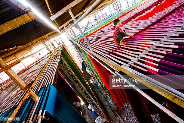 A child worker sits precariously working perched on a high wooden hanger the addan 20 meters high from the ground on January 10 2007 at a textile...