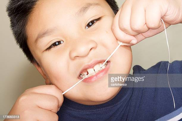 Child working to floss his front teeth