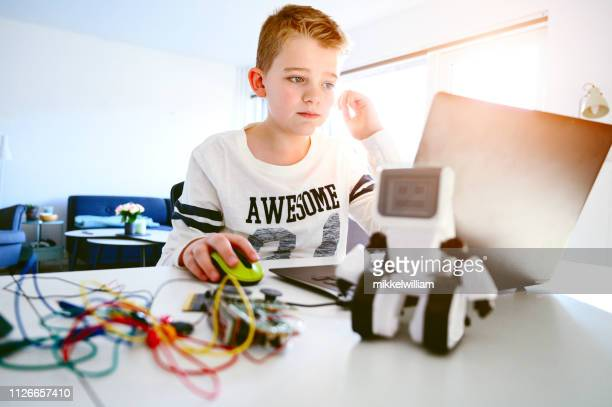 Child works with laptop and electronics and try to create a robot