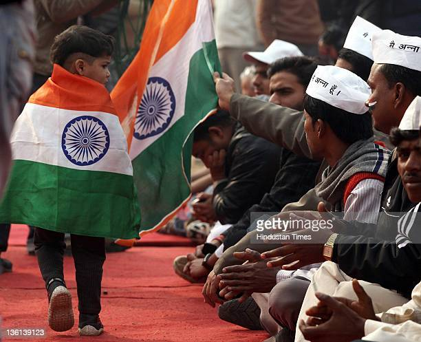 A child wrapped in an Indian tricolor looks on as supporters of Anna Hazare demonstrate for the Jan Lokpal bill at Ramlila Ground on December 27 2011...