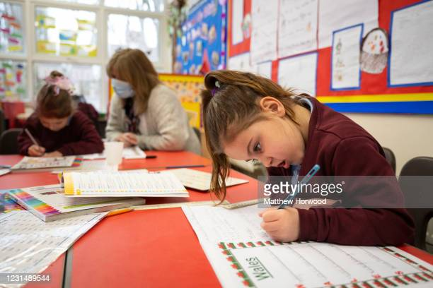 Child writes in a school book at Glan-Yr-Afon primary school on March 3, 2021 in Cardiff, Wales. Children aged three to seven began a phased return...