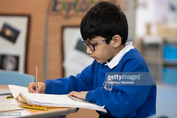 Child writes in a schoolbook at Roath Park Primary School on February 23, 2021 in Cardiff, Wales. Children aged three to seven began a phased return...