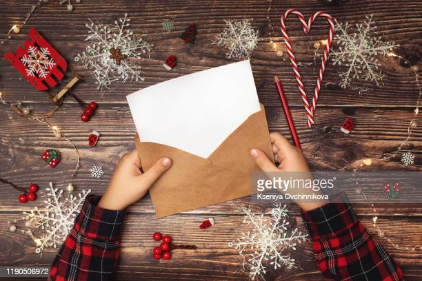 child writes the letter to santa claus. child's hands, the sheet of paper, pencils and christmas decorations on a wooden surface. concept of new year and christmas. top view - request stock pictures, royalty-free photos & images
