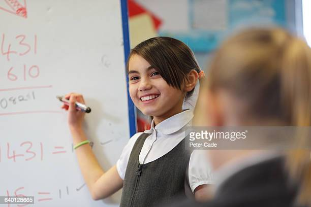 Child writing on board at front of class