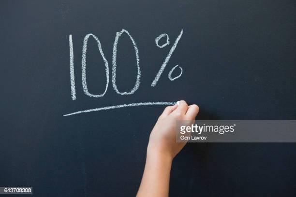 a child writing the word 100% on a blackboard - sinal de percentagem imagens e fotografias de stock