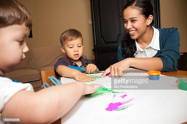 Childcare Worker Helping Two Young Boys with Fingerpaint
