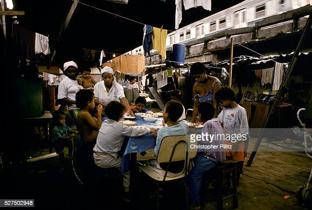Childen have lunch amidst the squalor of their slumb which lies under a Rio de Janeiro city overpass close to the world famous Maracana football...