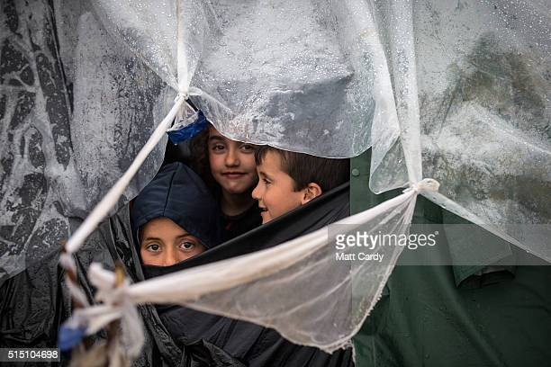 Childen look out from their tent as rain falls at the Idomeni refugee camp on the Greek Macedonia border on March 12 2016 in Idomeni Greece The...