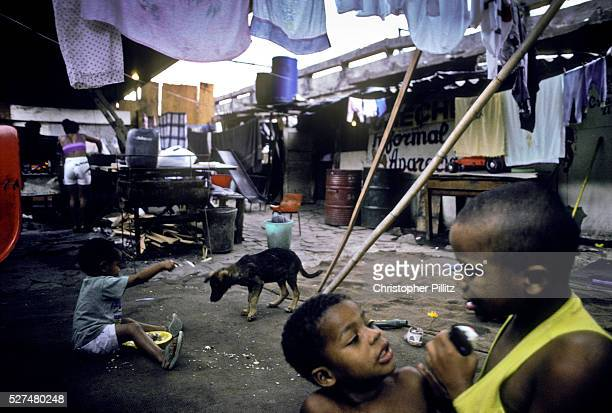 Childen play amidst the squalor of their slum which lies under Rio de janeiro city overpass Brazil