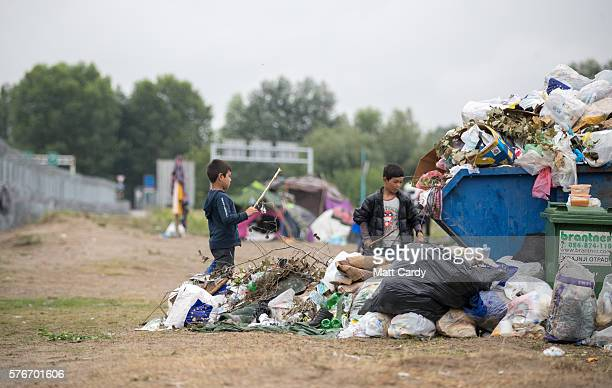 Childen play next to a skip full of rubbish at a informal camp besides the border fence close to the E75 Horgas border crossing between Serbia and...