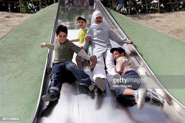 Childen play on a slide at the Jardins d'Acclimatation gardens while on a day out organized by the AFCL