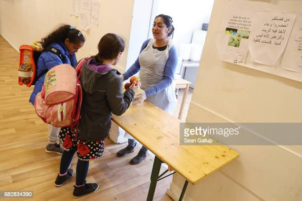 Childen who live at a shelter for refugees and migrants in Marienfelde district receive a snack in the shelter's cafeteria after they returned from...