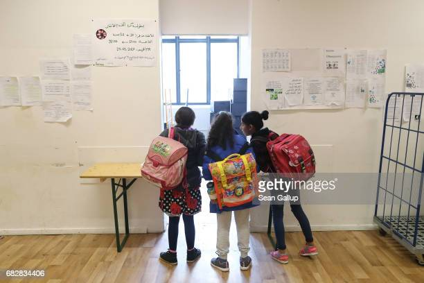 Childen who live at a shelter for refugees and migrants in Marienfelde district wait to receive a snack in the shelter's cafeteria after they...