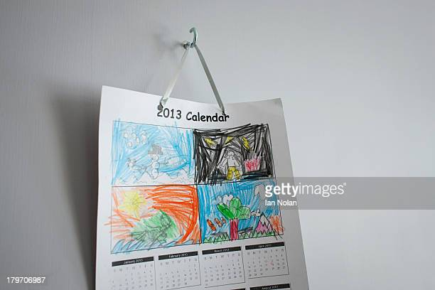 Childhood drawings on calendar hanging on wall