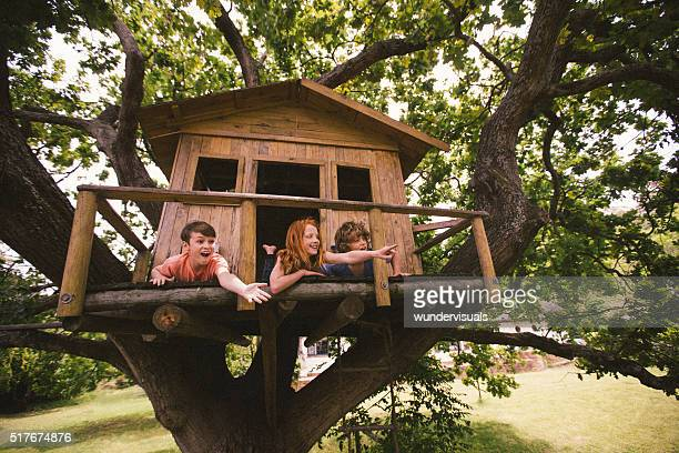 Childhood friends in a treehouse laughing and pointing