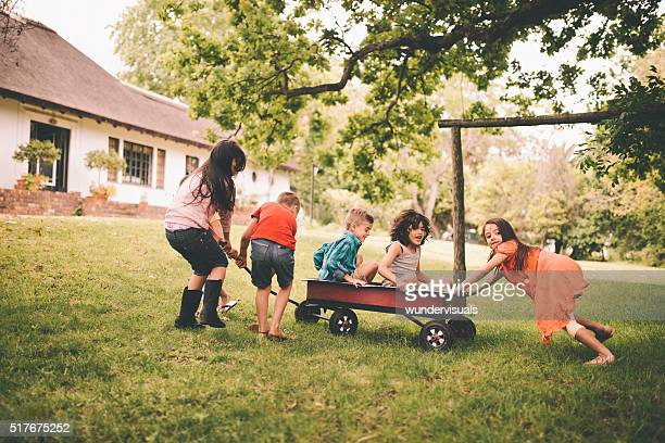 Childhood friends playing in a park together with a wagon