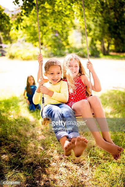 Childhood friends swinging happily together in natural park