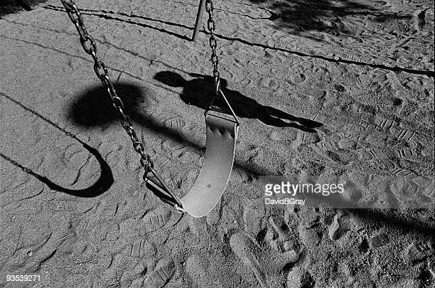 childhood memories : empty swing with child's shadow - child abuse stock pictures, royalty-free photos & images