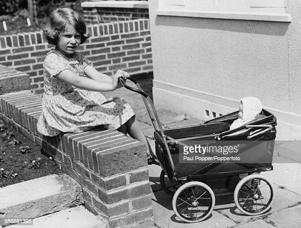 Childhood picture of Queen Elizabeth II with a toy doll in a pram in the grounds of the Royal Lodge at Windsor 1933