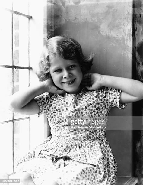 Childhood portrait of Queen Elizabeth II sitting in a window, August 12th 1932.