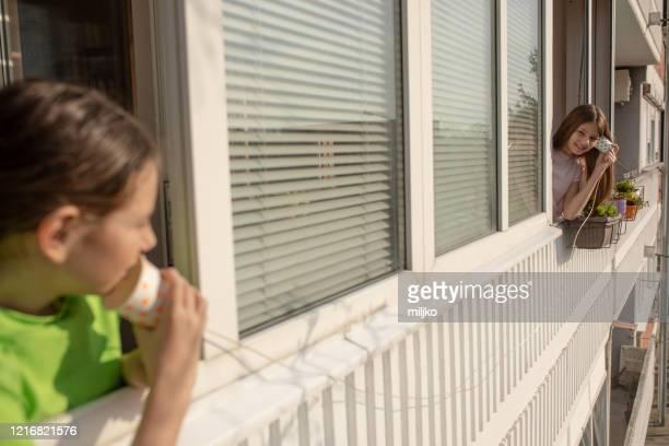 コロナウイルスの流行時に社会的な離散を伴う子供時代。 - 隣人 ストックフォトと画像