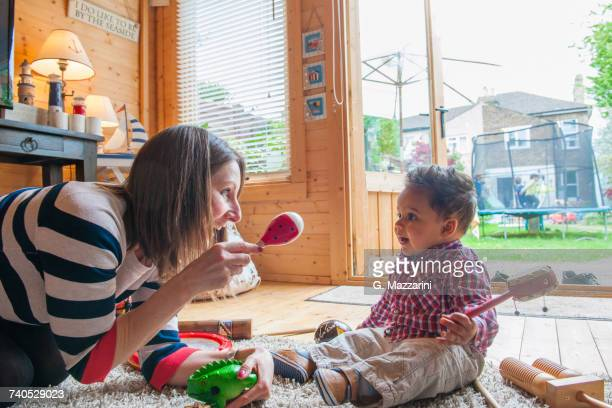 childminder shaking maraca at baby boy - nanny stock photos and pictures